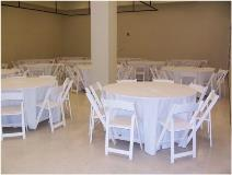 Round Table Setup with White Linens and White Resin Chairs